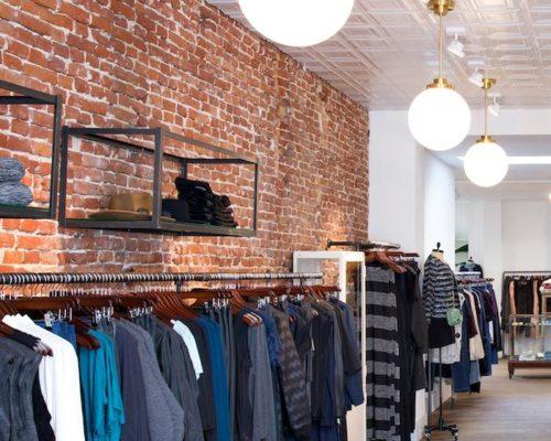 Witte stalen plafondtegels gecombineerd met baksteen muur voor een urban uitstraling bij trendy kledingzaak in Amsterdam