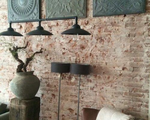 Stalen wandtegels als kunst aan bakstenen muur